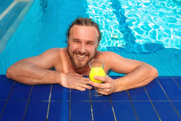 Jeune homme adulte européen caucasien gai avec des dreadlocks et barbe avec cocktail près de la piscine ouverte