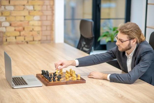 Jeune homme adulte à lunettes et costume réarrangeant la pièce d'échecs sur l'échiquier en face de l'ordinateur portable