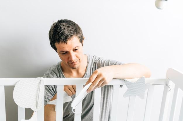 Jeune homme adulte préparant et décorant le berceau pour l'arrivée d'un bébé. nouveau concept de fils. parentalité et préparations