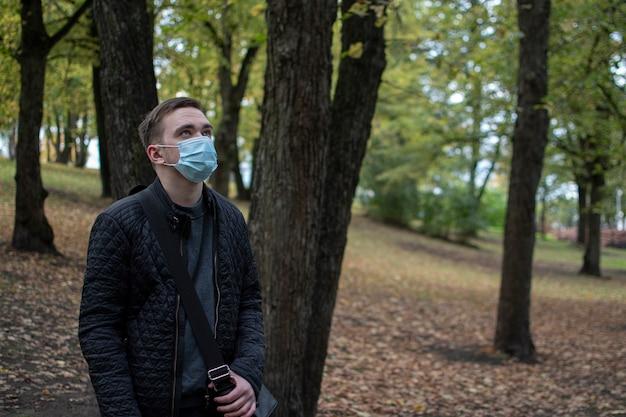 Un jeune homme adulte se tient dans un masque dans le parc regarde pensivement sur le côté, dans des vêtements sombres, un parc verdoyant