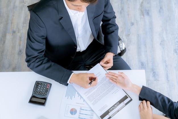 Un jeune homme d'affaires et un acheteur à la maison avaient atteint leur objectif ensemble et avaient été signés dans le contrat de vente de biens immobiliers