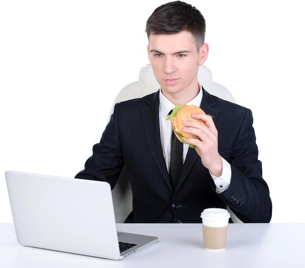 Jeune homme d'affaires affamé manger un hamburger.