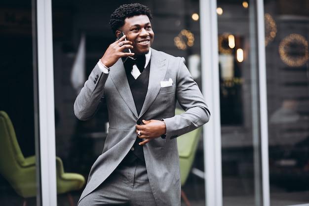 Jeune homme d'affaires africain à l'aide de téléphone