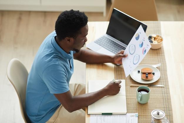 Jeune homme d'affaires africain assis à la table devant un ordinateur portable et examinant des documents pendant son petit-déjeuner à la maison