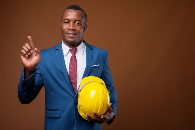 Jeune homme d'affaires africain avec casque sur fond marron