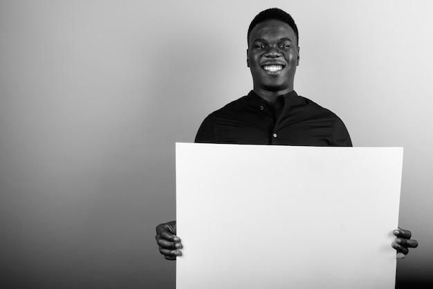 Jeune homme d'affaires africain contre le mur blanc. noir et blanc