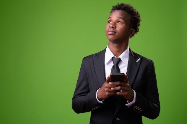 Jeune homme d'affaires africain contre le mur vert