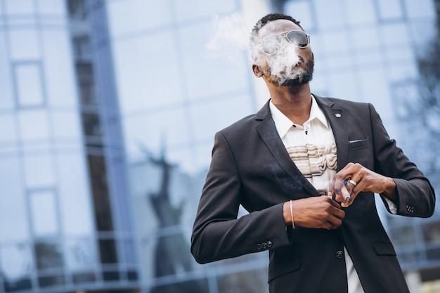 Jeune homme d'affaires africain en costume chic cigarette fumer