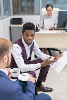 Jeune homme d'affaires africain discutant du papier avec son collègue