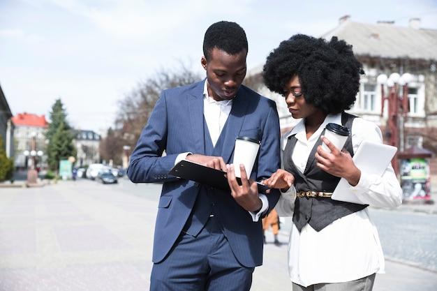 Jeune homme d'affaires africain et femme d'affaires à la recherche dans le presse-papiers