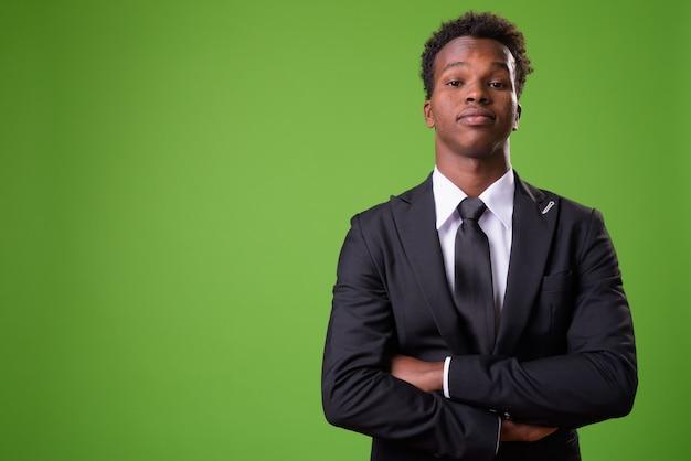 Jeune homme d'affaires africain sur fond vert