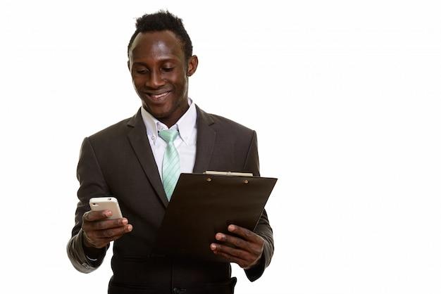 Jeune homme d'affaires africain heureux souriant et utilisant un téléphone portable