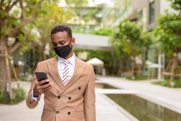 Jeune homme d'affaires africain avec masque à l'aide de téléphone dans la ville avec la nature