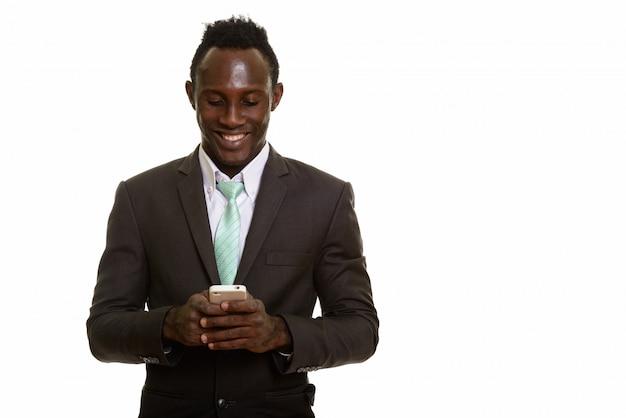 Jeune homme d'affaires africain noir heureux souriant tout en utilisant le mobile
