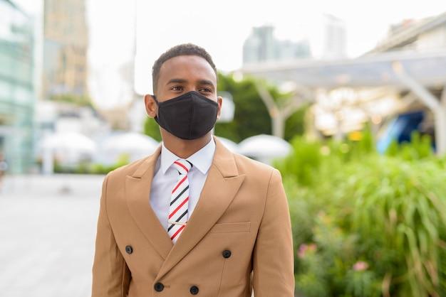 Jeune homme d'affaires africain pensant avec un masque pour se protéger contre l'épidémie de coronavirus dans les rues de la ville