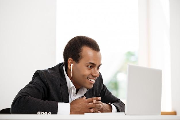 Jeune homme d'affaires africain réussi dans les écouteurs souriant, regardant un ordinateur portable.