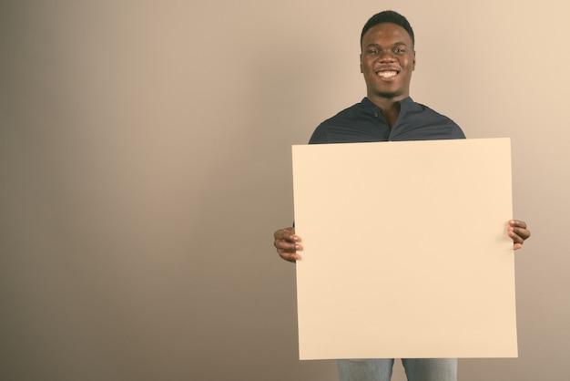Jeune homme d'affaires africain tenant un tableau blanc