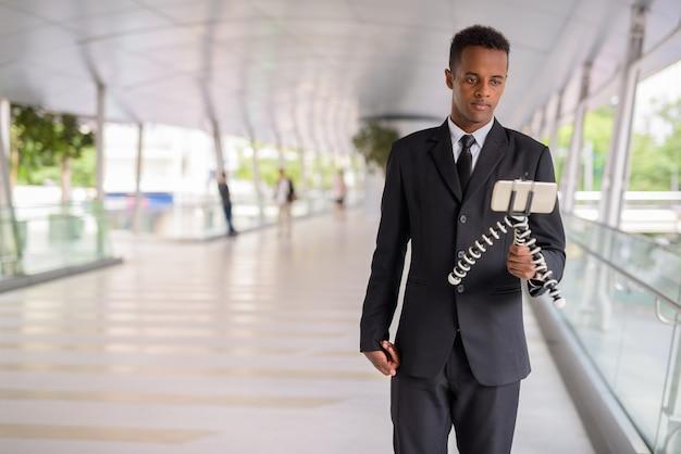 Jeune homme d'affaires africain utilisant un téléphone mobile et vlogging à l'extérieur en ville