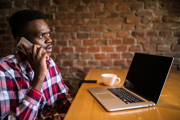Jeune homme d'affaires afro-américain attrayant avec des lunettes et un ordinateur portable assis dans un café-bar et utiliser un téléphone portable.