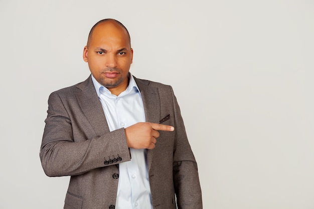 Jeune homme d'affaires afro-américain avec une expression coquette, pointant son doigt et fronçant les sourcils, plissant les yeux dans la confusion, pensant sérieusement à un problème difficile.