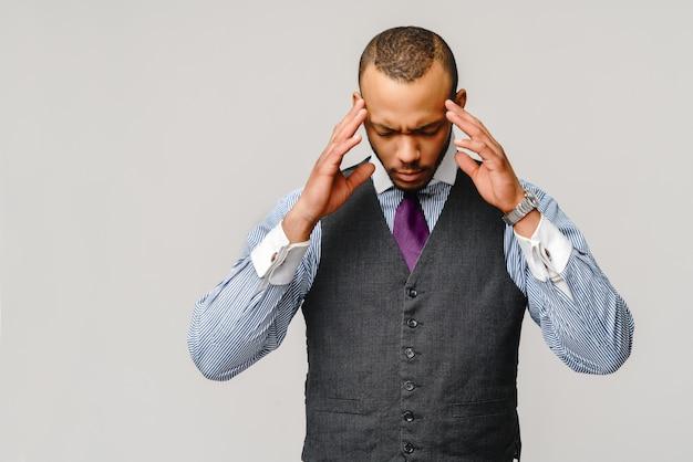 Jeune homme d'affaires afro-américain touchant la tête à cause de maux de tête et de stress.