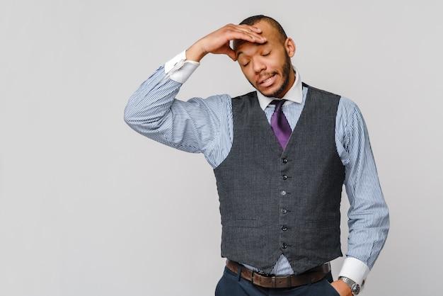 Jeune homme d'affaires afro-américain touchant la tête à cause de maux de tête et de stress