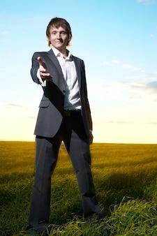 Jeune homme d'affaires aide la main dans le champ