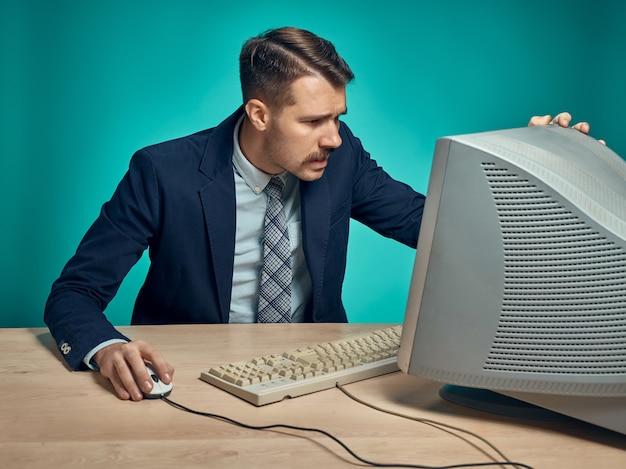 Jeune homme d'affaires à l'aide d'ordinateur au bureau