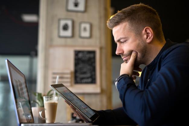 Jeune homme d'affaires à l'aide d'une tablette et d'un ordinateur portable dans un café-bar analysant des projets.