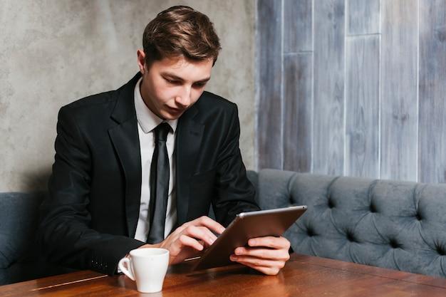 Jeune homme d'affaires à l'aide de tablette