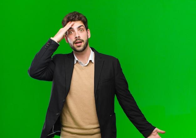 Jeune homme d'affaires à l'air heureux, surpris et surpris, souriant et réalisant des bonnes nouvelles incroyables et incroyables vert