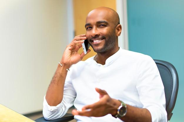 Jeune homme d'affaires américain afro au bureau à l'aide de téléphone portable