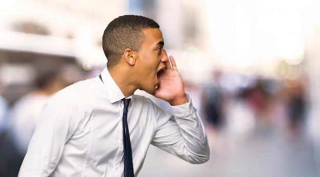 Jeune homme d'affaires américain afro criant avec la bouche grande ouverte sur le côté de la ville