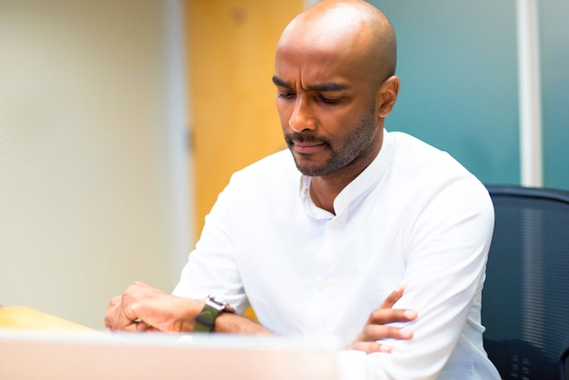 Jeune homme d'affaires américain afro dans le bureau à la recherche de la montre