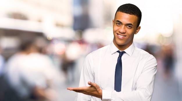 Jeune homme d'affaires américain afro présentant une idée tout en regardant en souriant vers la ville
