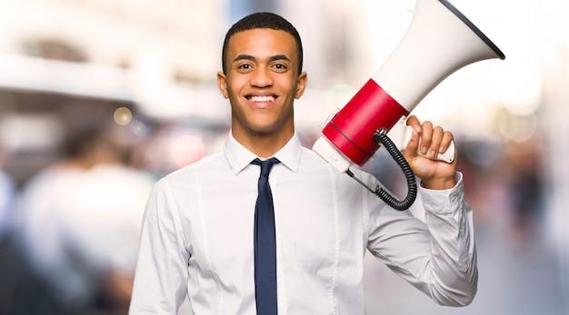 Jeune homme d'affaires américain afro tenant un mégaphone dans la ville