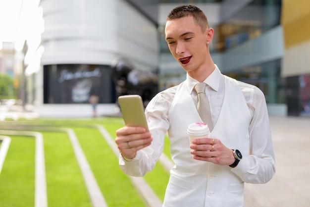 Jeune homme d'affaires androgyne à l'aide de téléphone