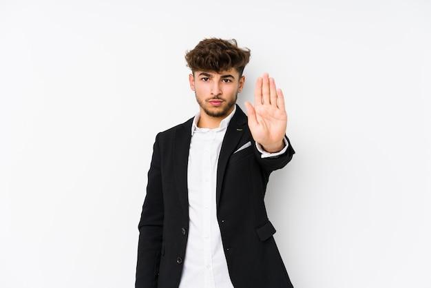 Jeune homme d'affaires arabe isolé debout avec la main tendue montrant le panneau d'arrêt, vous empêchant.