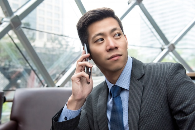 Jeune homme d'affaires asiatique appelant sur un téléphone mobile