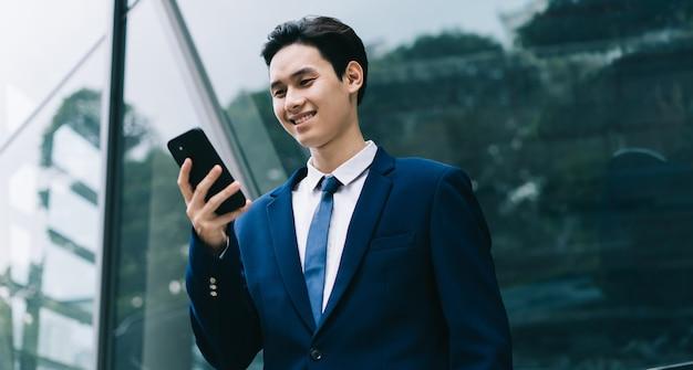 Jeune homme d'affaires asiatique avec bâtiment en verre