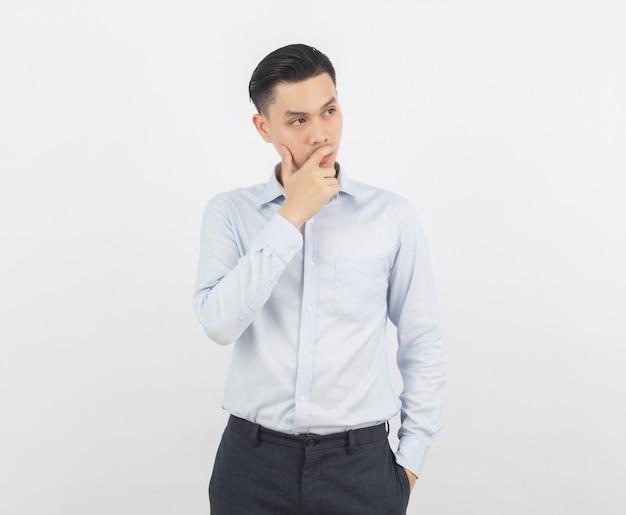 Jeune homme d'affaires asiatique beau penser une idée tout en levant