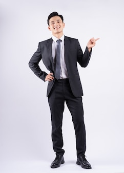 Jeune homme d'affaires asiatique debout sur blanc