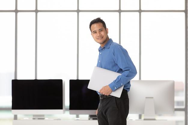 Jeune homme d'affaires asiatique debout et tenant le nouvel ordinateur portable avec bonheur dans le bureau moderne, groupe d'ordinateurs de bureau flou dans behide.