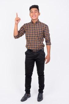 Jeune homme d'affaires asiatique heureux pointant vers le haut contre le mur blanc