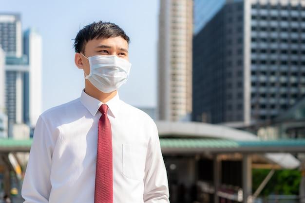 Jeune homme d'affaires asiatique intelligent en chemise blanche va travailler dans la ville de la pollution, il porte un masque de protection pour empêcher la poussière de pm2,5, le smog, la pollution de l'air et covid-19