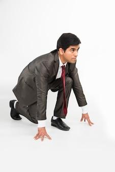 Jeune homme d'affaires asiatique intelligent et déterminé en cours d'exécution ou debout en position de départ, isolé sur blanc