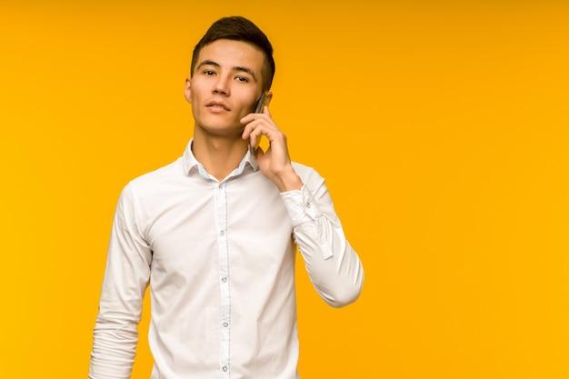 Jeune homme d'affaires asiatique masculin parle sérieusement au téléphone.