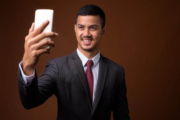 Jeune homme d'affaires asiatique multiethnique contre mur marron