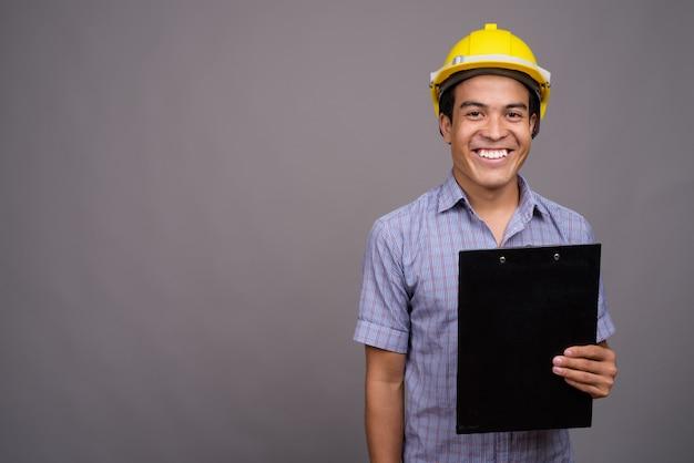 Jeune homme d'affaires asiatique portant un casque tout en tenant le presse-papiers contre le mur gris