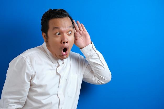 Un jeune homme d'affaires asiatique portant une chemise blanche écoute des chuchotements avec une grimace. curieuse. écoutez attentivement les potins juteux. nouvelles de conversation, violation de la vie privée, contre le mur bleu